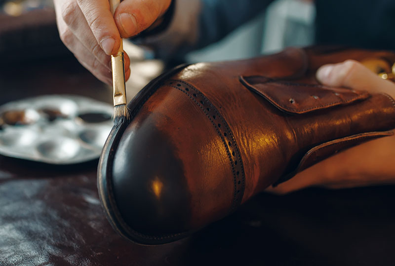 Foto von Schuster, der Politur auf Schuh pinselt