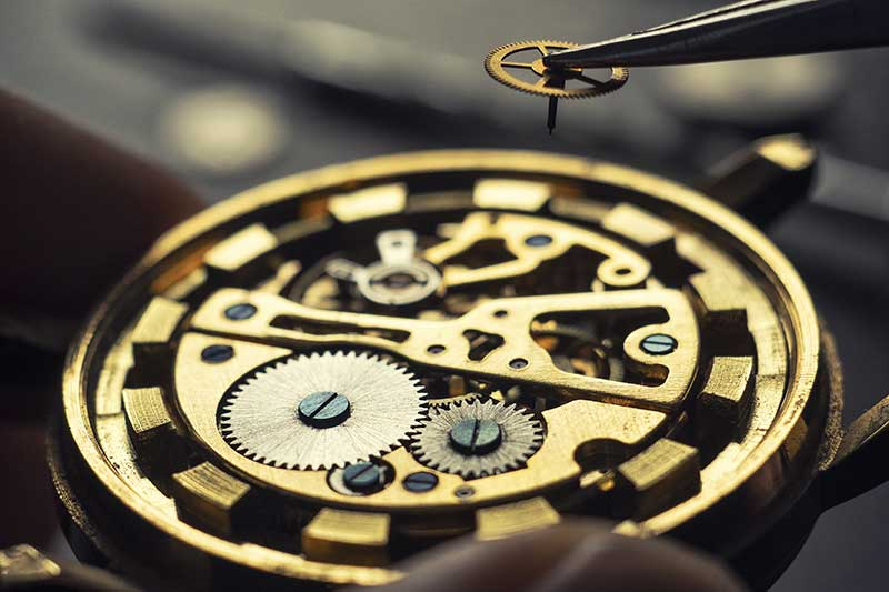 Foto mit Fokus auf Uhrwerk und Uhrmacher, der Rädchen mit Pinzette hält